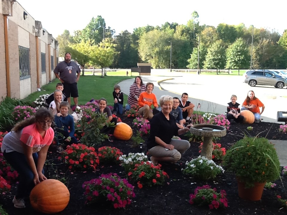 5th Grade students plant flowers, MH class waters flowers and out PTO president donates pumpkins