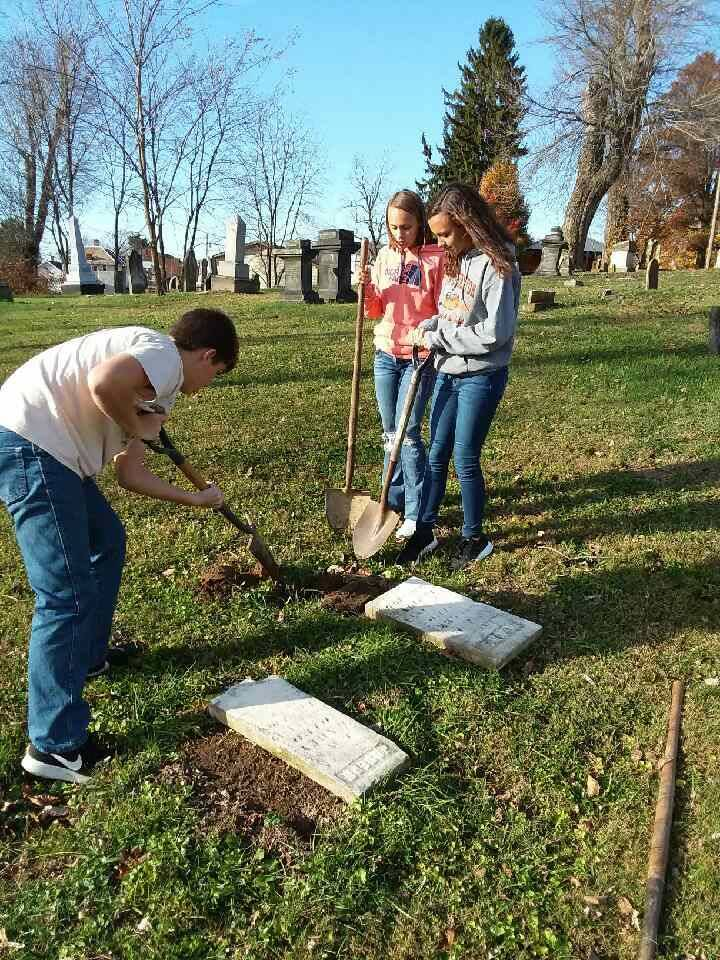 Service Club students resetting gravestones.