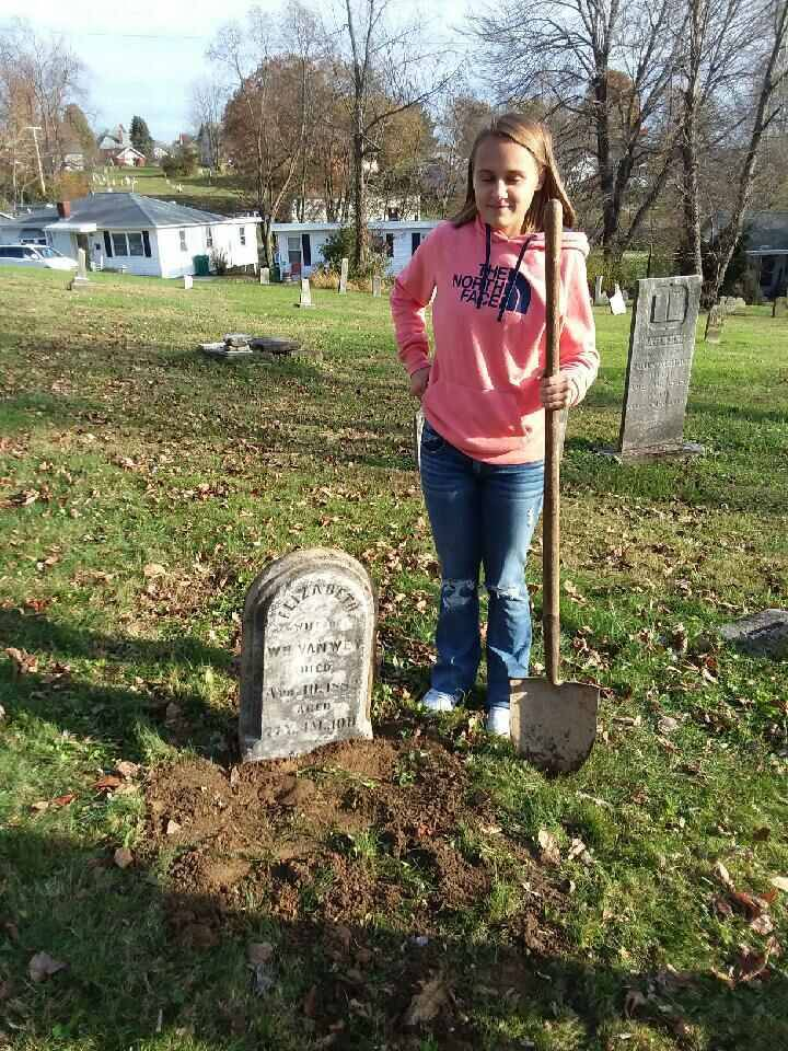 Student helping to reset a gravestone.